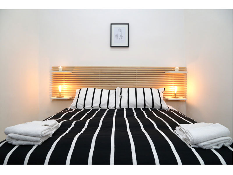 Camera da letto toni neutri con testata in legno