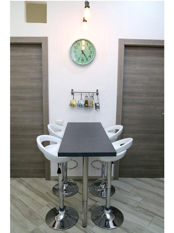 Cucina living, dettaglio del tavolo sneak con sgabbelli e accessori applicati a muro