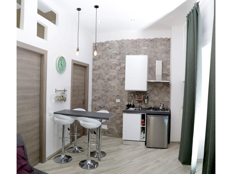 Cucina living con angolo cottura e tavolo sneack con sgabelli