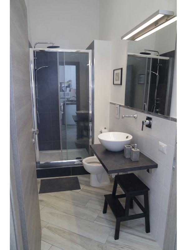 Bagno con lavabo da appoggio e cabina doccia a incasso
