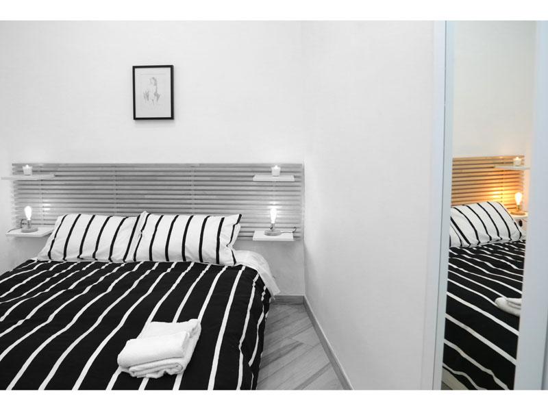 Dettaglio camera da letto colori chiari con armadio a specchio