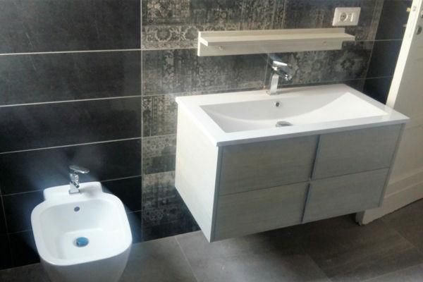 Bagno con rivestimenti in gres porcellanato, mobile bagno effetto legno chiaro
