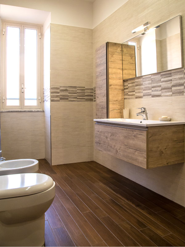 Bagno con rivestimenti in gres porcellanato color sabbia mobile lavabo in legno