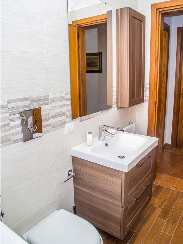 mobile bagno in legno con cassettoni e lavabo bianco integrato