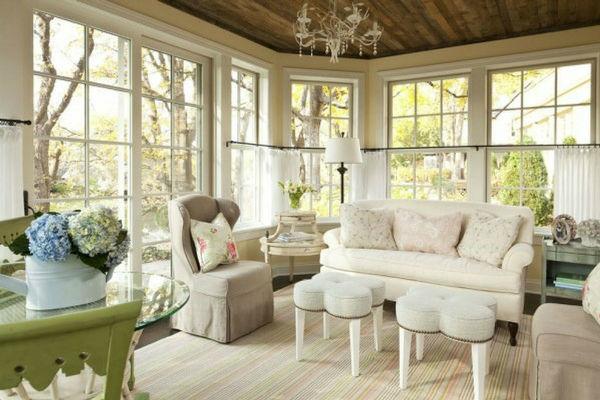 salotto in veranda con divano e poltrone chiare e tavolini pouff