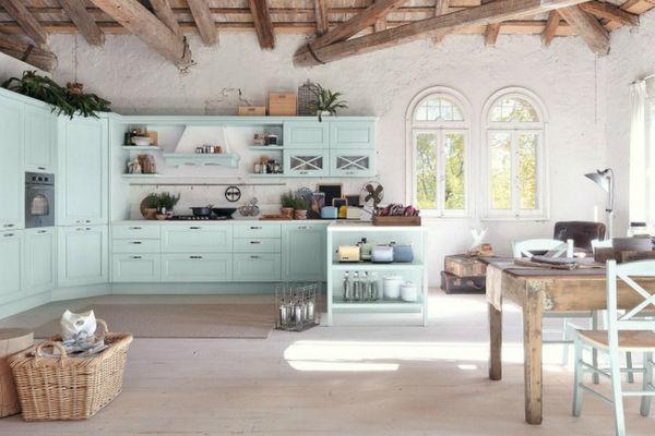 Cucina con arredo celeste soffitto con travi in legno a vista