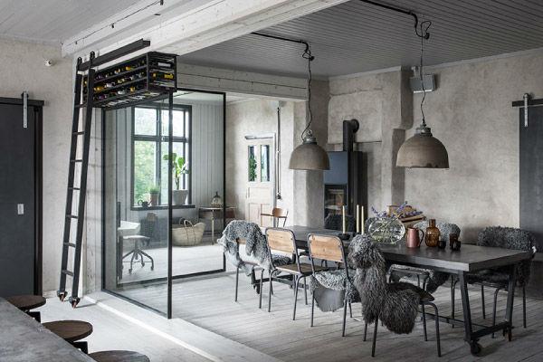 Sala pranzo con tavolo e sedie lavorate in ferro pavimento effetto legno grigio