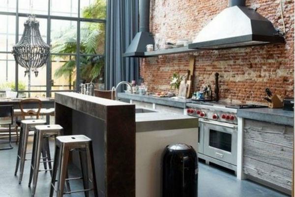 cucina con isola centrale rivestimento in mattoni rossi grezzi
