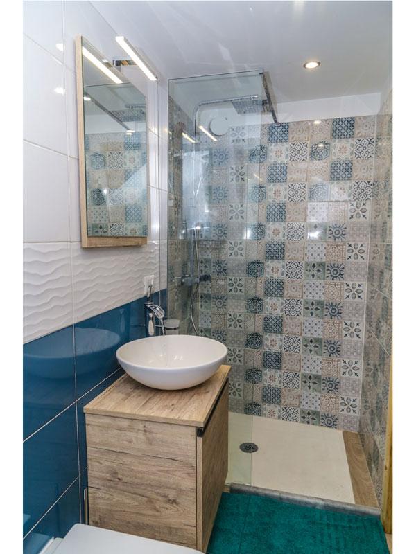 bagno rivestimento ceramica color bianco e blu, mobile bagno in legno con lavabo da appoggio
