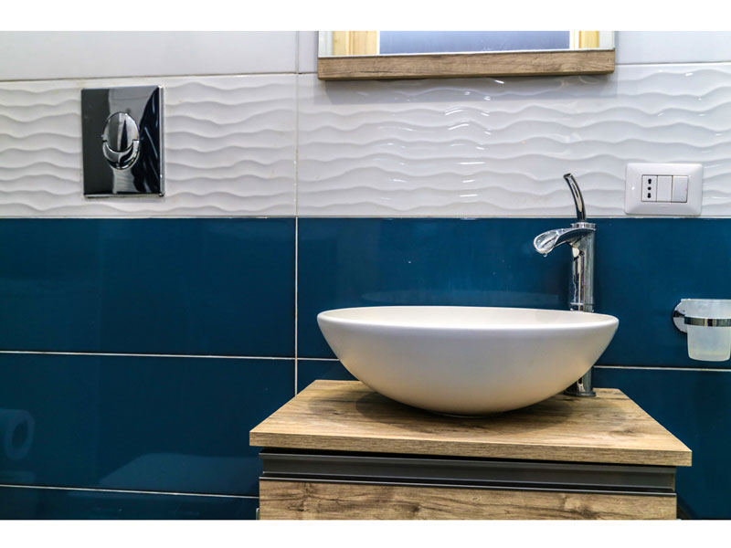 Bagno con rivestimenti in ceramica blui e bianco, lavabo da appoggio