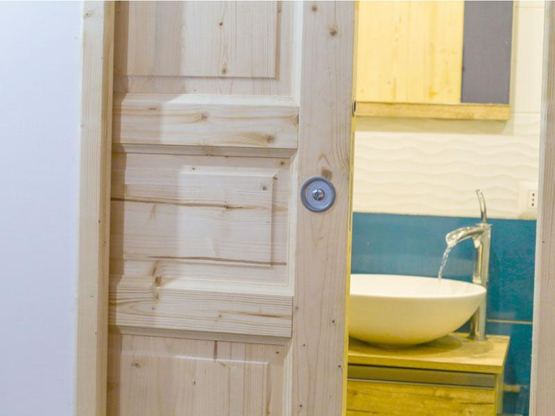 Porta scorrevole in legno grezzo e stanza bagno
