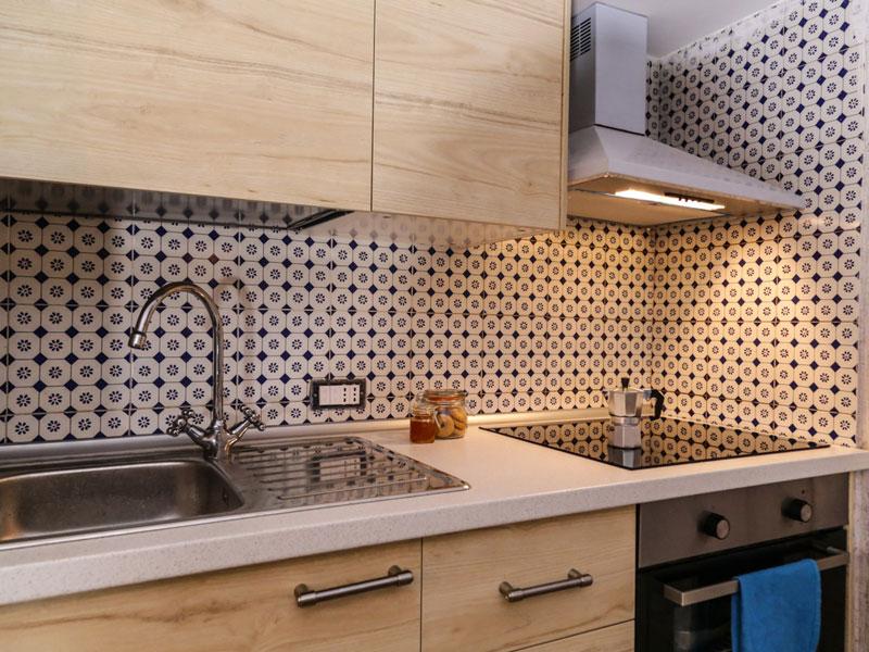 Piccola cucina a vista rivestimento in maiolica e mobili in legno