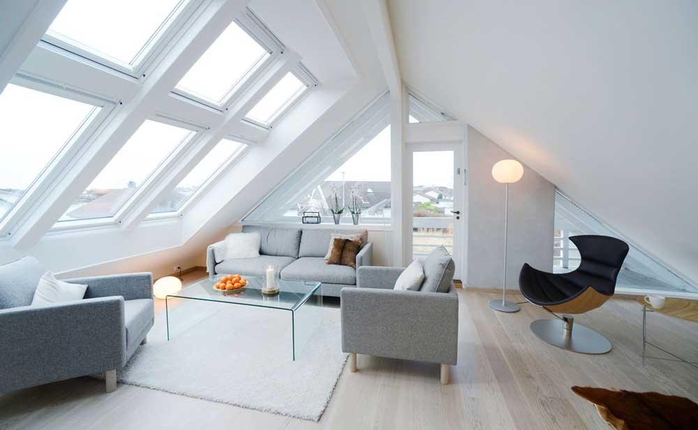 Ampia vetrata in zona salotto con divanetti e sofa grigi