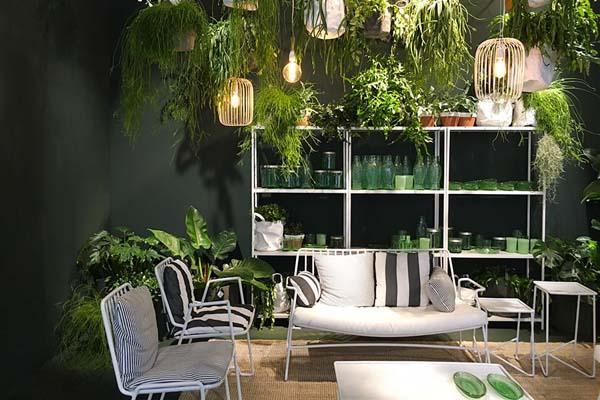 Salone in stile Jungle con credenza avvolta da varie tipologie di piante da interno