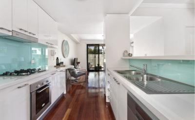 Cucina bianca con elementi in acciaio e rivestimento in resina verde acqua