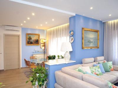 Salone living con pareti azzurre e divano grigio