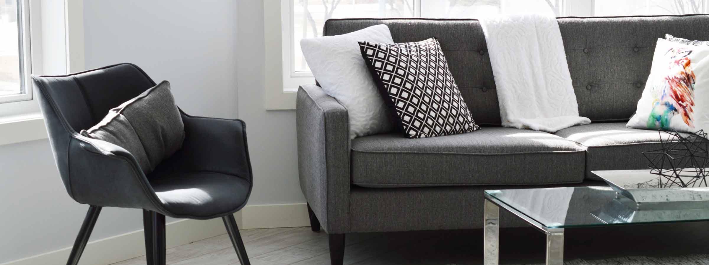 Vista di un salone con poltroncina nera e divano con cuscini ricamati