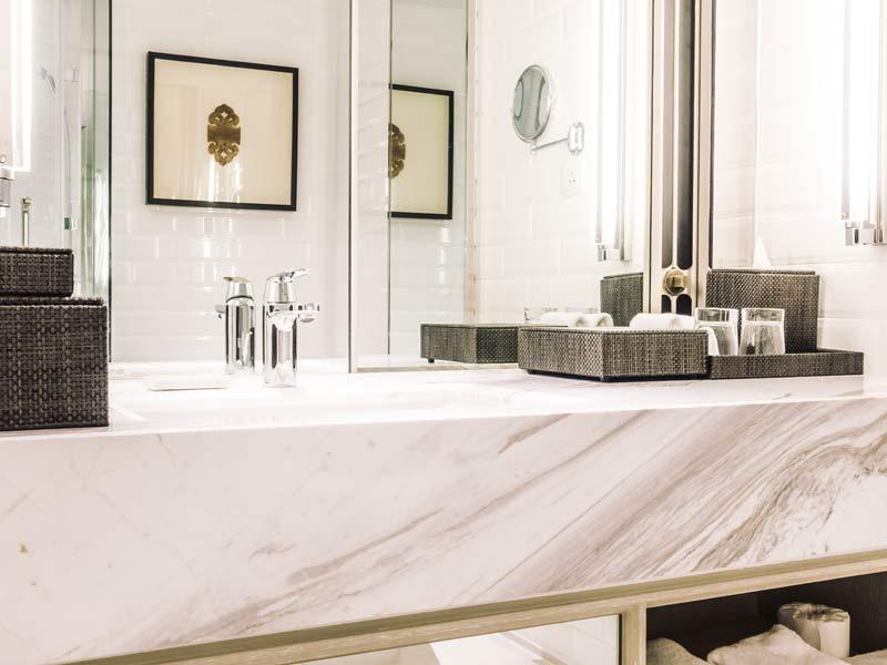Dettaglio di un lavabo in marmo del bagno padronale con doppio specchio e rubinetteria in acciaio lucido.