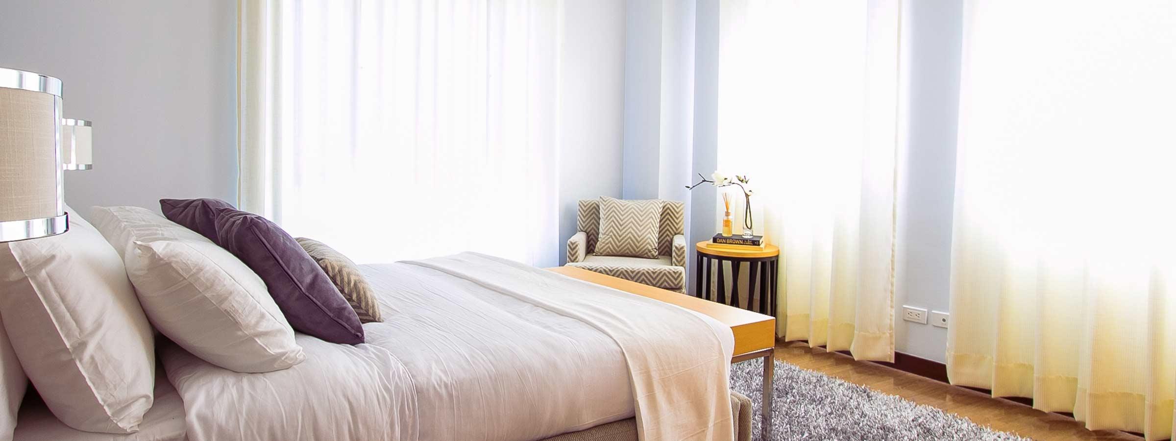 Camera da letto con matrimoniale, nell'angolo una poltroncina con tavolino e tre tende ad abbellire le pareti.