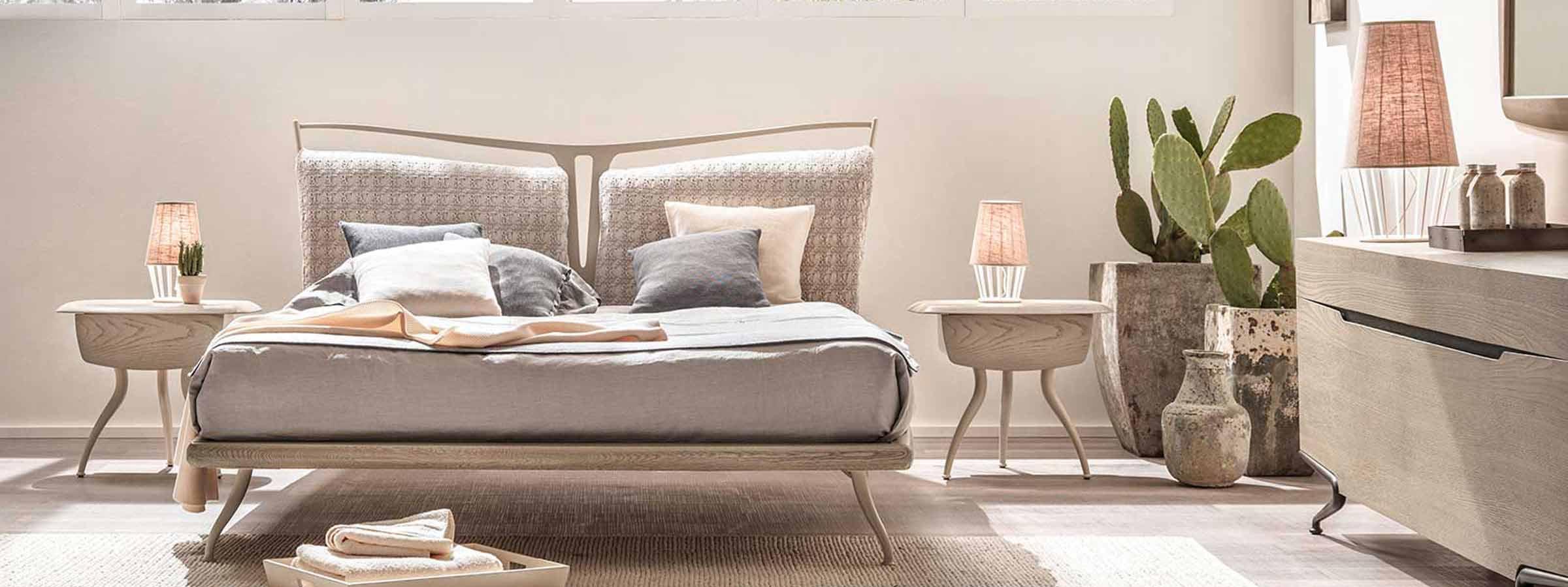Vista di una camera da letto con letto matrimoniale, comodini in legno e cassettiera. Nell'angolo delle splendide piante grasse.