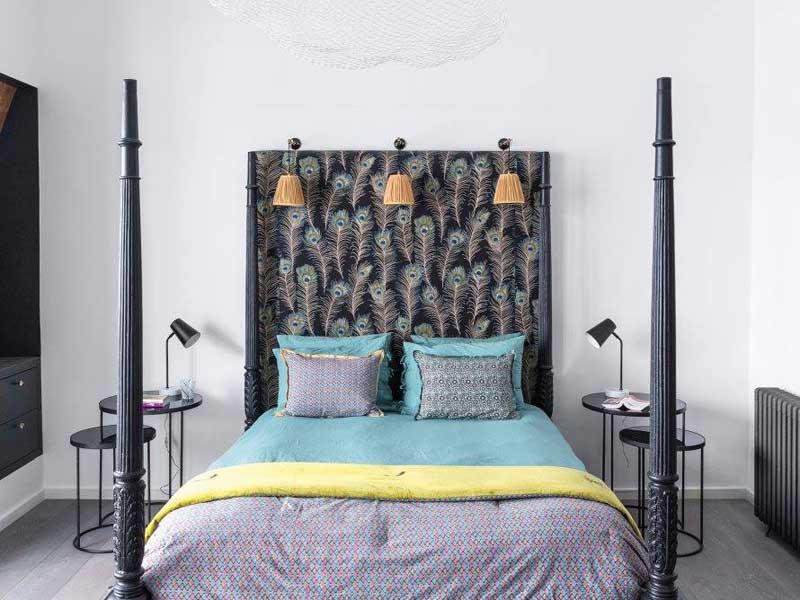 Camer da letto dai colori scuri con letto matrimoniale con testata a tema code di pavone.
