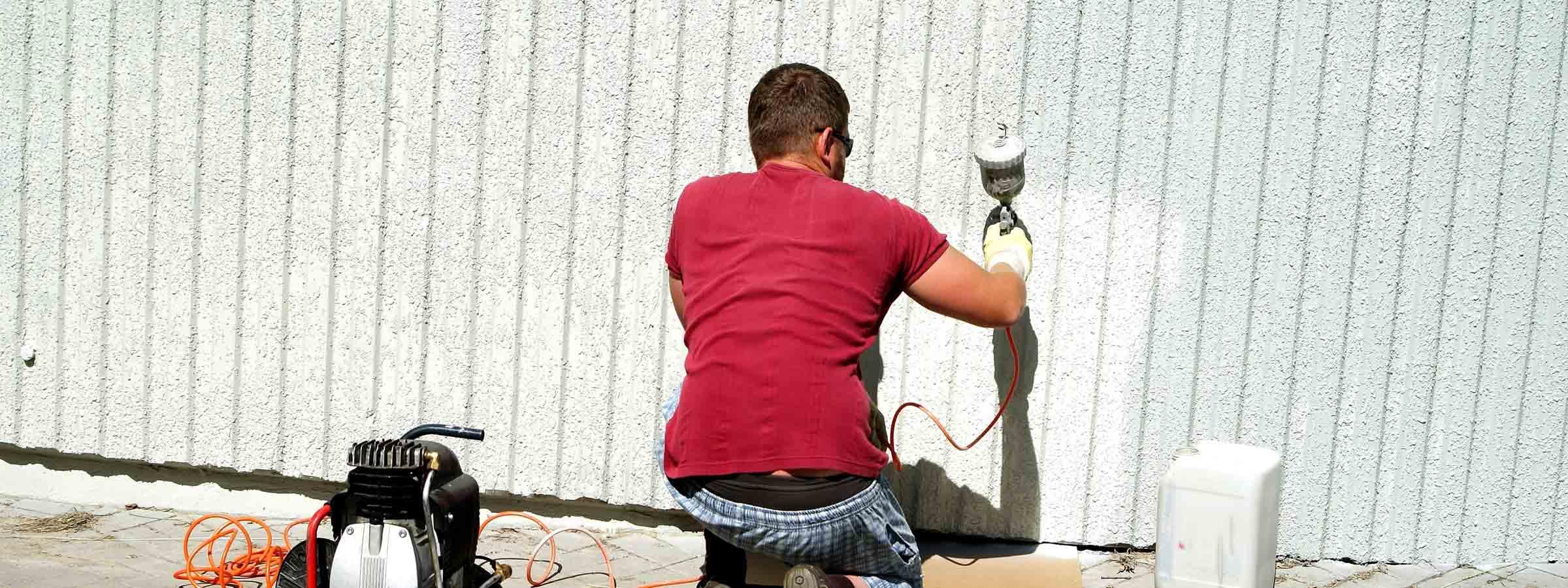 Operaio all'opera mentre tinteggia le pareti esterne di un edificio