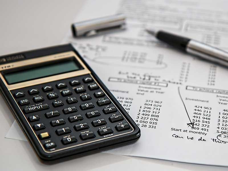 Calcolatrice adagiata su di un foglio dove ci sono il segnate le cife di spesa per la ristrutturazione