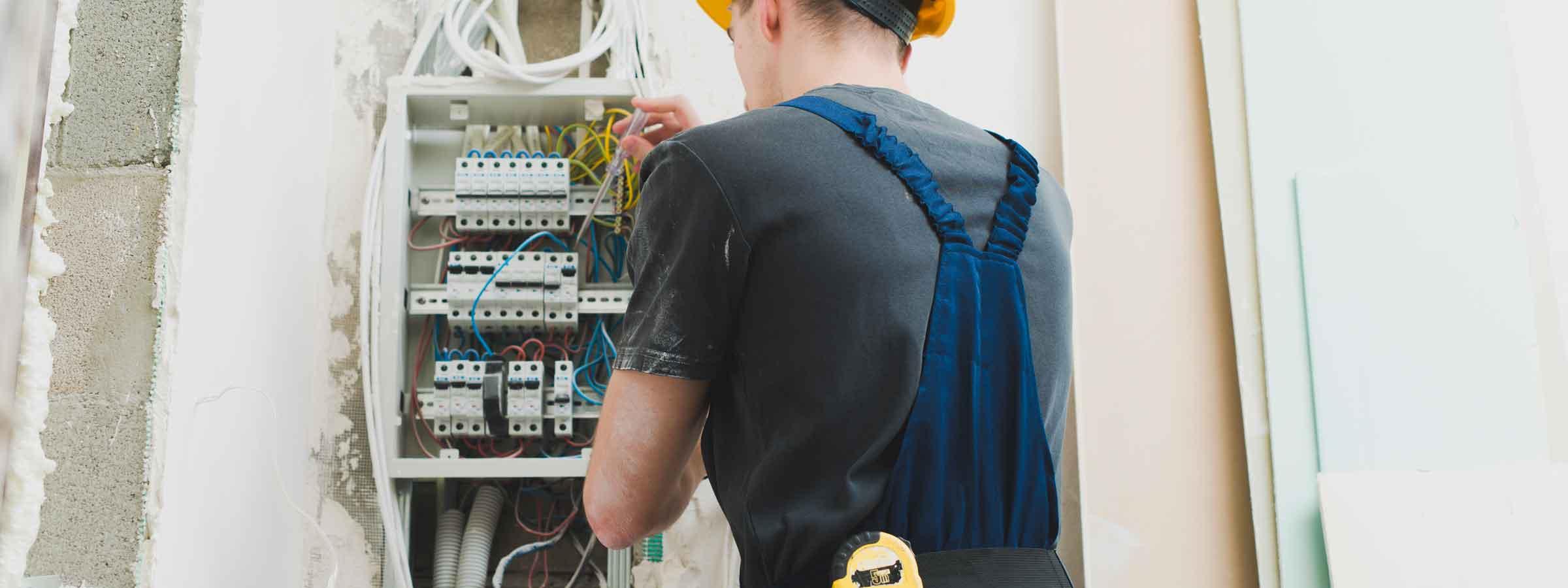 Operaio specializzato al lavoro su un quadro elettrico per ristrutturare l'impianto.