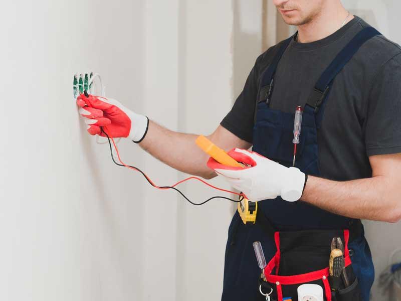 Operaio specializzato intento alla misurazione del voltaggio dell'impianto elettrico