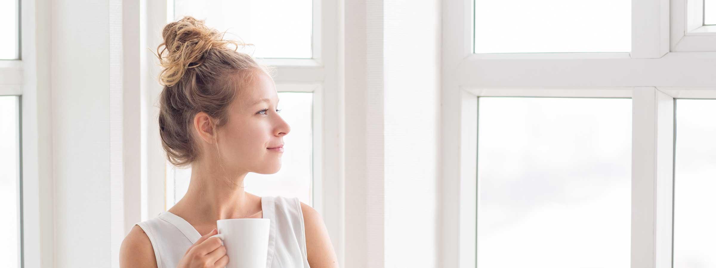 Ragazza guarda dalla finestra mentre fa colazione