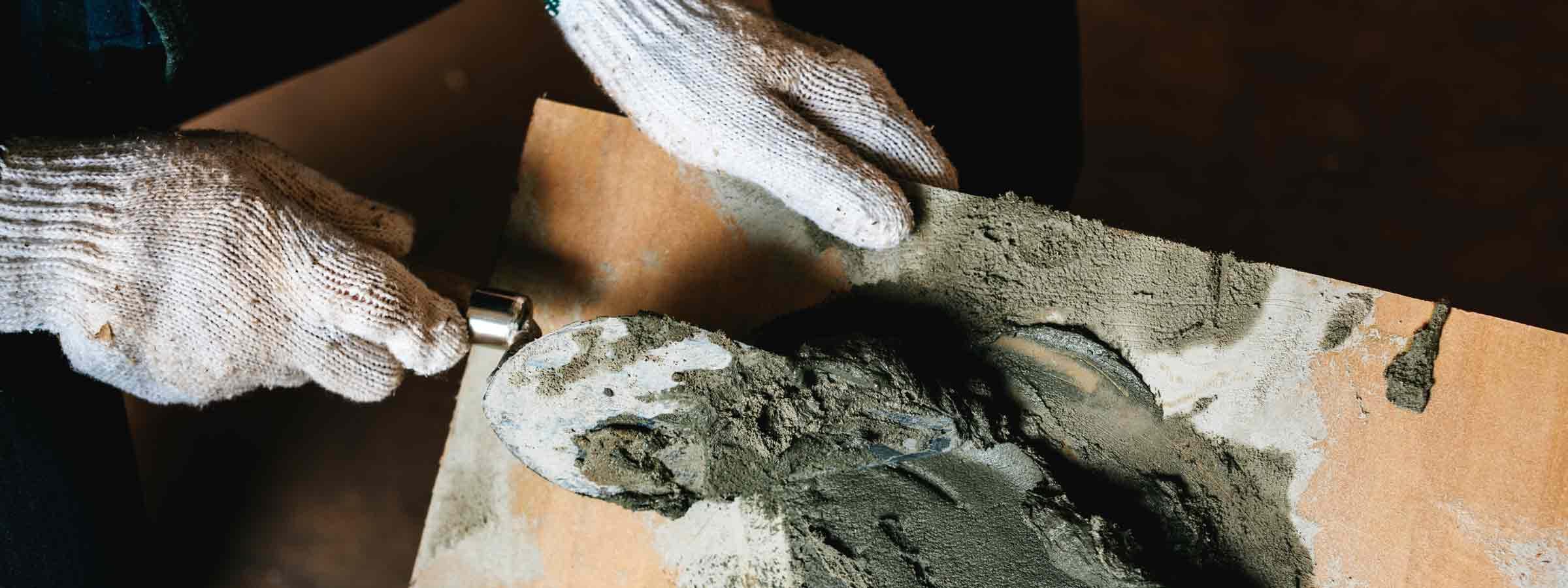 Operaio mentre stende la calce su una superficie in legno