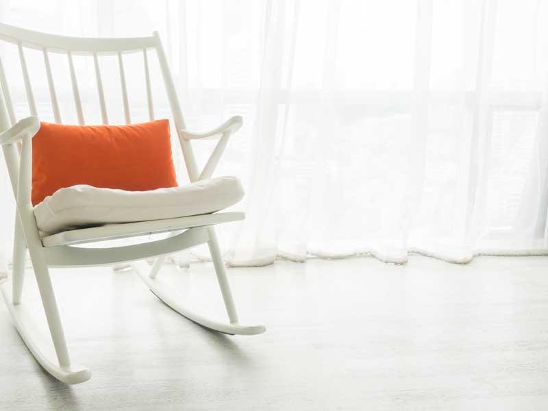 Sedia a dondolo bianca su pavimento in grès porcellanato