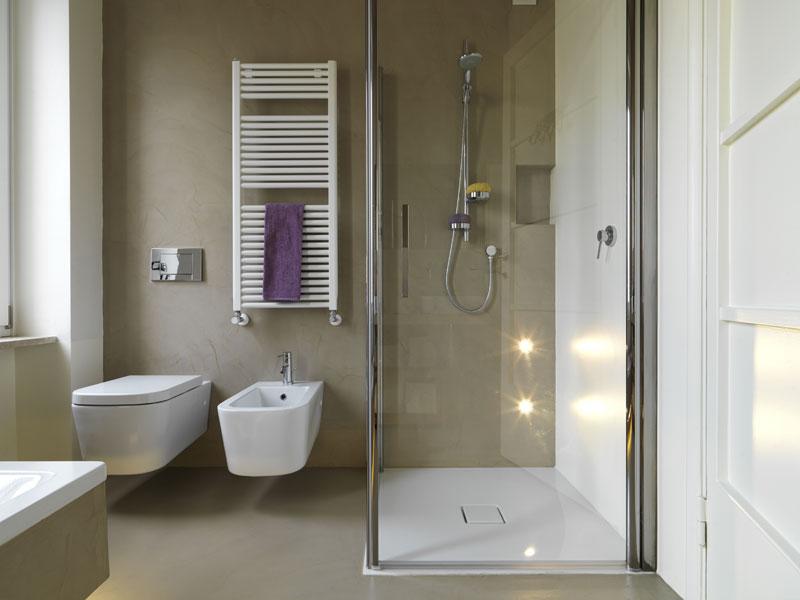 Bagno di servizio con doccia con porte di vetro e sanitari filomuro con termosifone di design.
