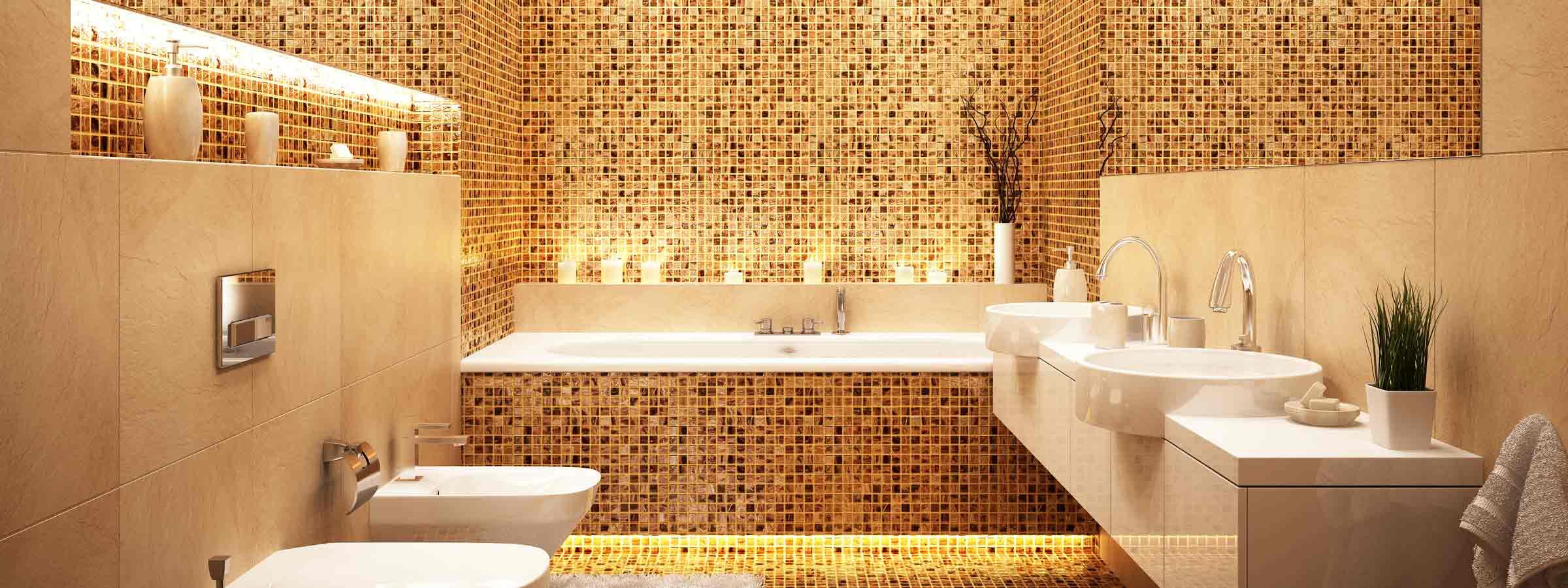 Bagno piastrellato con bvasca al centro, sulla sinistra wc e bidet e sulla destra doppio lavabo e specchio.