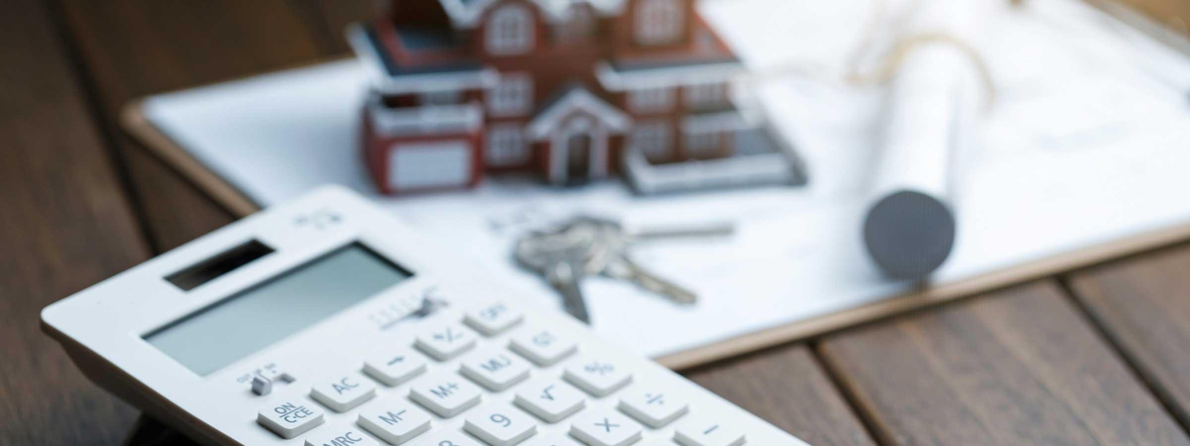 Calcolatrice adagiata sul pavimento con un modellino di casa e un mazzo di chiavi