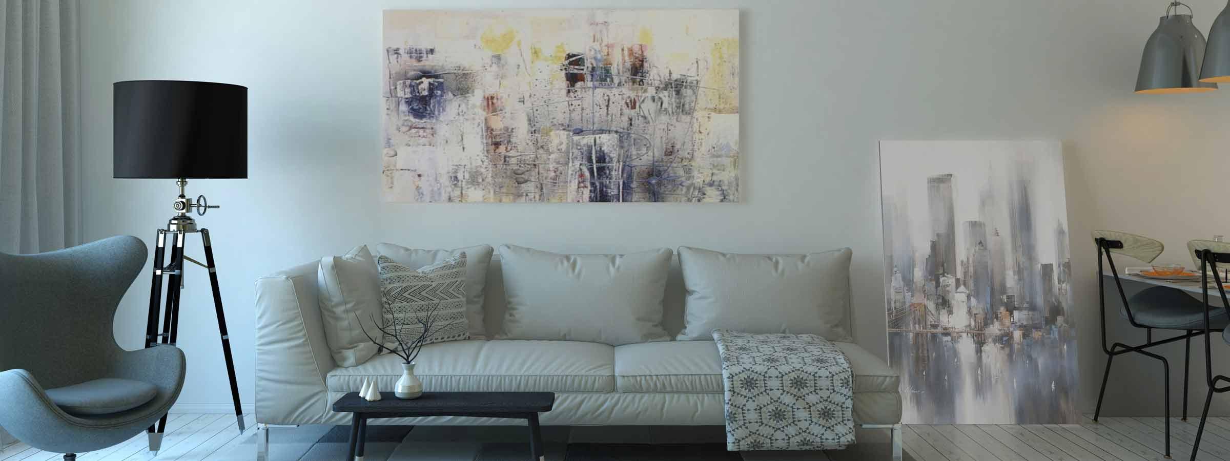 Soggiorno con arredamento stile industriale dai colori neutri e quadri con riferimenti alle metropoli urbane