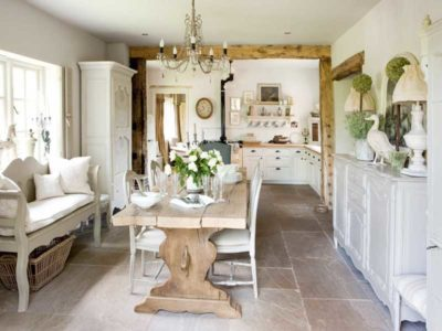 Salone in stile shabby chic con tavolo da pranzo in legno e travi in vista