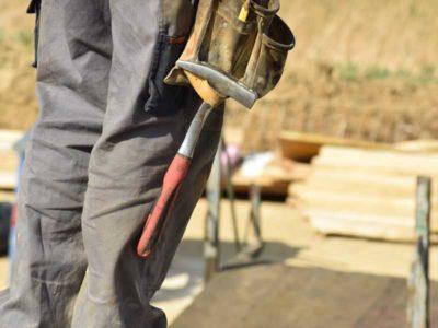Operaio in piedi con alla vita una cintura per attrezzi con all'interno un martello