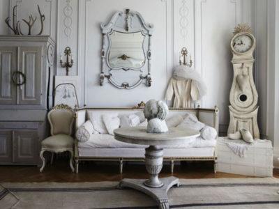 Salone arredato in shabby con divano, tavolino circolare, mobiletto e orologio pendente ad angolo