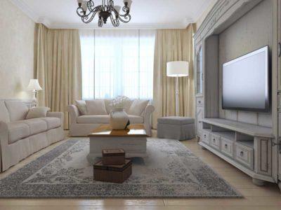 Salone arredato in stile shabby con doppio divano, tavolino e parete attrezzata in tinte beige