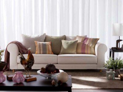 Vista frontale di una salone arredato in stile classico con un divano in stoffa beige ricoperto di cuscini dai colori tenui.