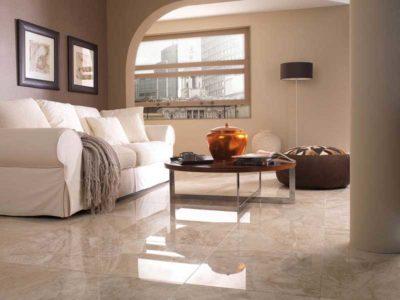 Vista di un salone arredato in stile classico con pavimento in marmo, divano doppio e tavolino in legno.