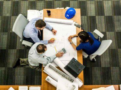 Addetti ai lavori edili che progettano una costruzione secondo le ultime norme urbanistiche