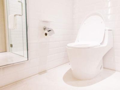 Vista di una toilette con water con copriwater e porta cara igienica