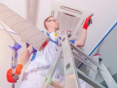 Operaio su scaletto intento a ridipingere durante una ristrutturazione