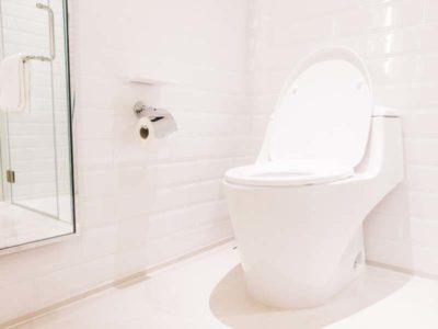Vista di un bagno a tinte rosa con sanitari a terra filomuro