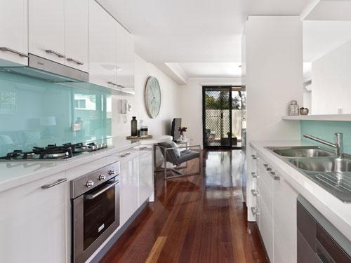 Vista laterale di una cucina a vista bianca con dettagli in argento e celeste