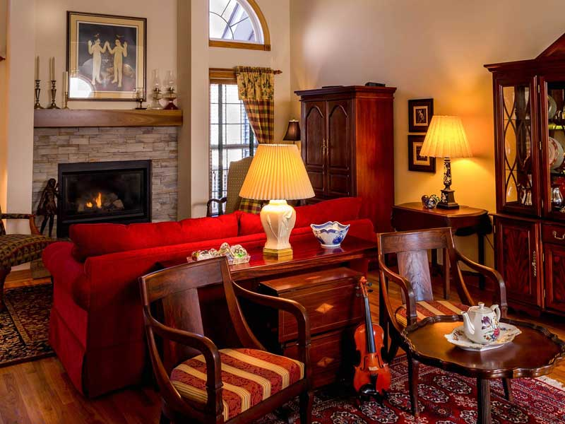 Soggiorno in stile country con divano rosso e colori intensi e camino.