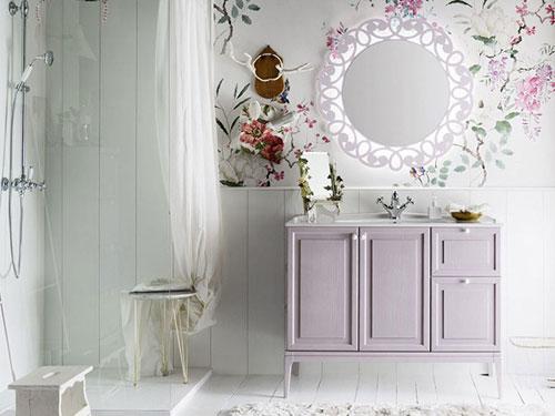 Vista di un bagno in stile shabby chic con mobiletto lilla e specchio con fantasia floreale
