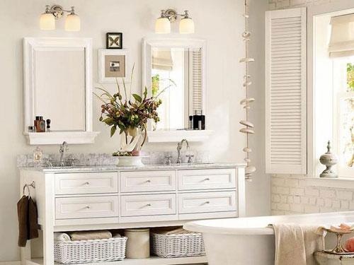 Vista di un bagno in stile shabby chic con vasca in primo piano e mobile con doppio lavandino e doppio specchio.
